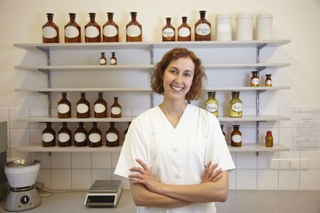 Female pharmacist standing in lab with shelf photo