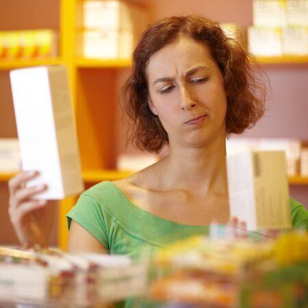 desconfianza: Cliente femenino en la comparaci�n de dos medicamentos de farmacia