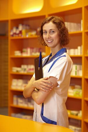 Female pharmacist with clipboard behind pharmacy counter Stock Photo - 6053456