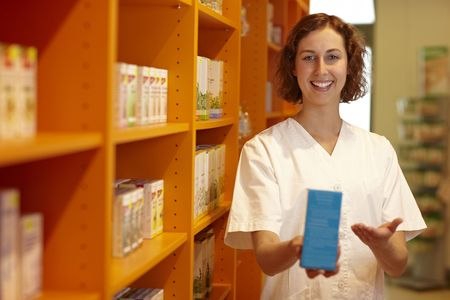 Female pharmacist pointing to medicine in her hand Stock Photo - 6053533