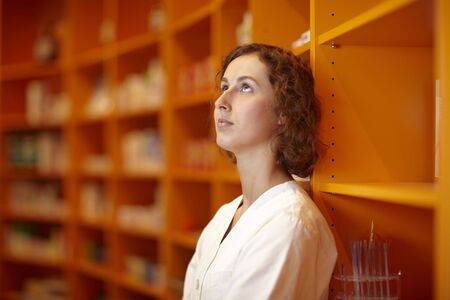 Pharmacist leaning on pharmacy shelf and looking up photo