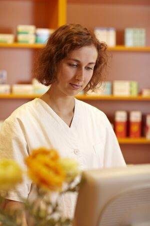 Pharmacist typing on computer behind pharmacy counter Stock Photo - 6066781