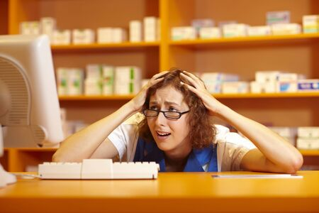 Pharmacist looking desperately at computer in pharmacy photo