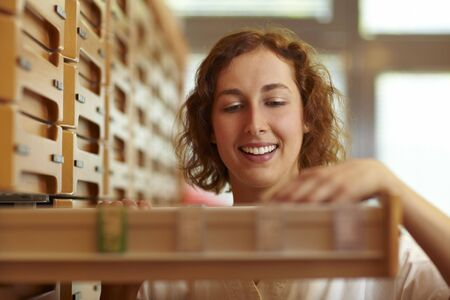 Pharmacist reaching for drawer at medicine cabinet Stock Photo - 6066871