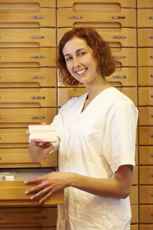 Female pharmacist at medicine cabinet in pharmacy photo