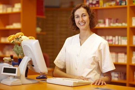 Happy pharmacist standing behind counter in pharmacy Stock Photo - 6066811