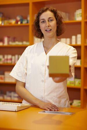 Female pharmacist behind counter explaining usage of medicine photo