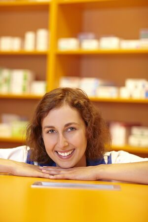 Happy female pharmacist behind counter in pharmacy photo