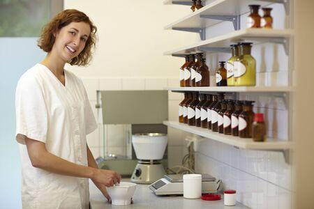 formulation: Happy female pharmacist preparing medication with mortar