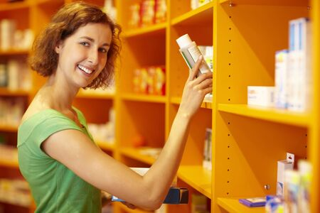 Happy customer taking medicine from a shelf photo