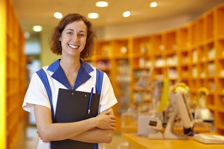 the seller: Happy female pharmacist with clipboard in pharmacy