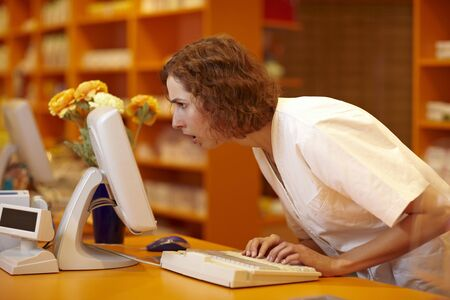 Pharmacist looking surprised at computer monitor in pharmacy photo