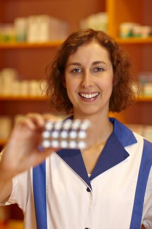 Happy pharmacist holding many pills in hand photo