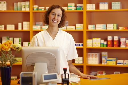 Happy pharmacist standing behind counter in pharmacy photo