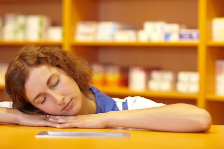 Female pharmacist sleeping with head on counter Stock Photo - 6066853