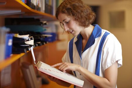 adverse reaction: Female pharmacist reading in a red book