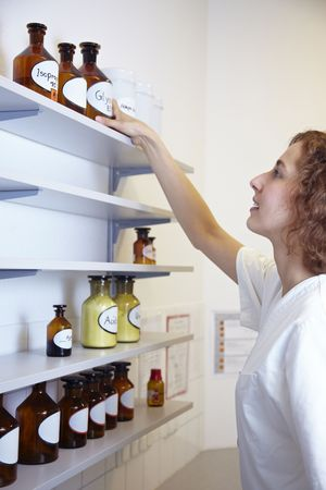 formulation: Pharmacist in lab reaching for bottle with alcohol