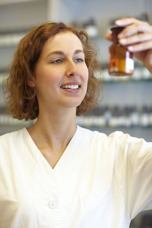 Pharmacist taking a look at Calciumchlorid in pharmacy Stock Photo - 6066843