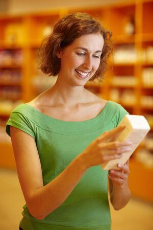 Customer in pharmacy reading information in medicine photo
