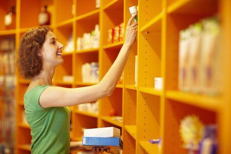 Happy customer taking medicine from a shelf photo