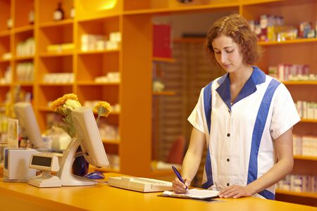 Female pharmacist filling out questionnaire in pharmacy photo