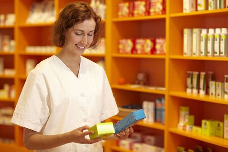Female pharmacist looking at medicine in her hand photo