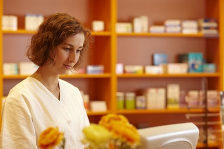 Pharmacist typing on computer behind pharmacy counter Stock Photo - 6066874