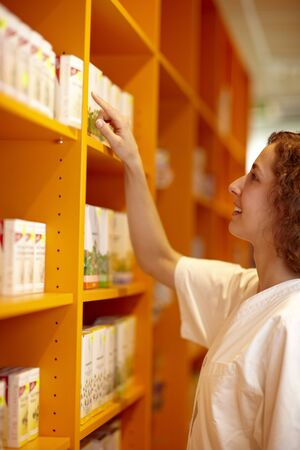 Female pharmacist looking for medicine in shelf photo