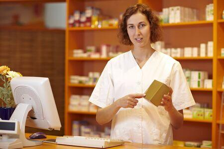 Female pharmacist behind counter explaining usage of medicine Stock Photo - 6066875