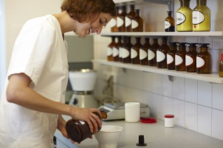 Female pharmacist mixing drug ingredients in lab photo