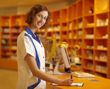 Female pharmacist signing contract at pharmacy counter Stock Photo - 6066909