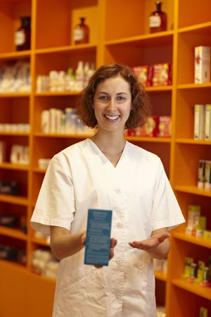 Female pharmacist pointing to medicine in her hand photo