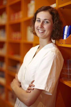 Portrait of a pharmacist leaning on shelves in pharmacy photo
