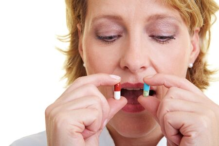 Blonde woman looking at two pills in her hands Stock Photo - 6200288