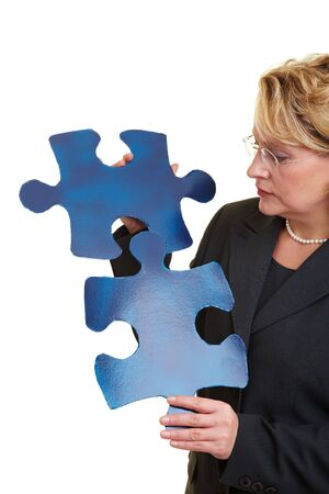 Business woman holding two blue jigsaw pieces photo