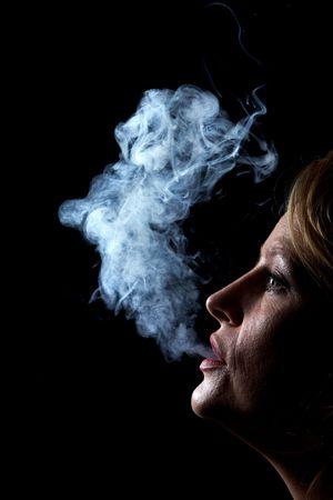 Woman exhaling cigarette smoke on black background