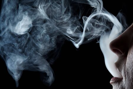 Mouth exhaling cigarette smoke on black background Stock Photo