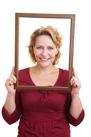 self conceit: Happy woman holding a wooden frame in front of her face