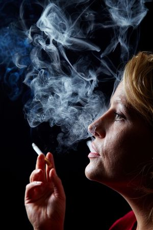 smoker: Woman exhaling cigarette smoke on black background