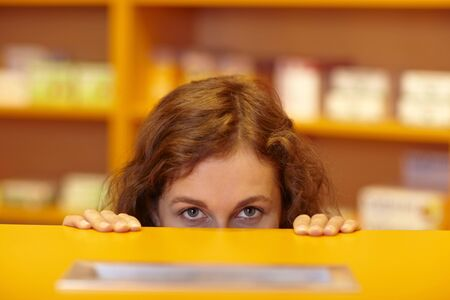 hideout: Female pharmacist looking up behind counter in pharmacy Stock Photo