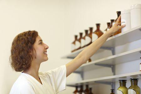 Pharmacist putting drug bottle in shelf in lab photo