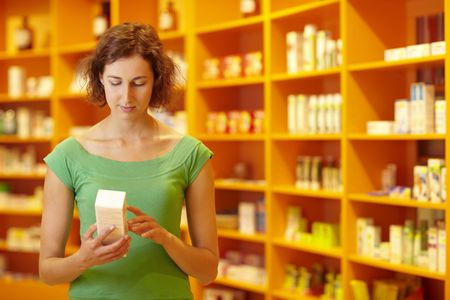 adverse reaction: Customer in pharmacy reading information on medicine Stock Photo