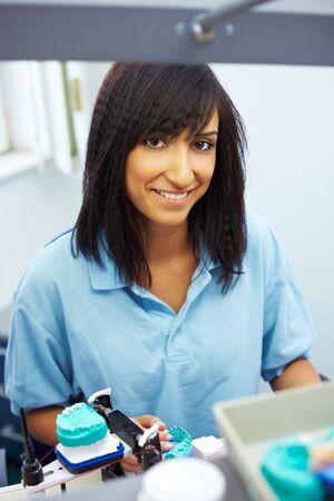 articulator: Happy dental technician working on an articulator