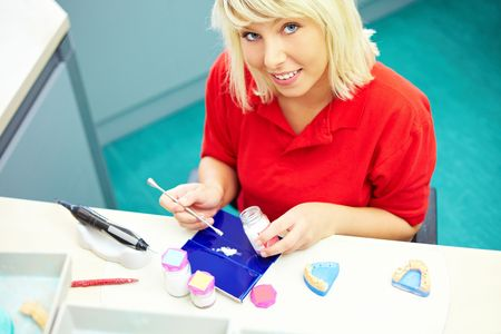 Dental technician preparing ceramic powder for dentures photo