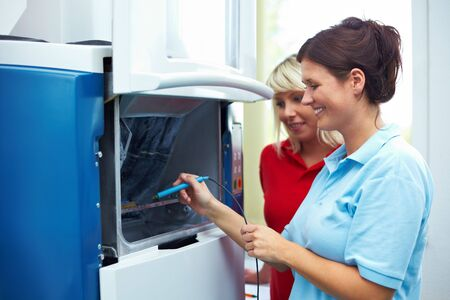 dental nurse: Dental technician scanning a chip for a CAM