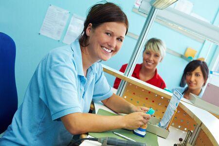 Three dental technicians working in a dental laboratory photo