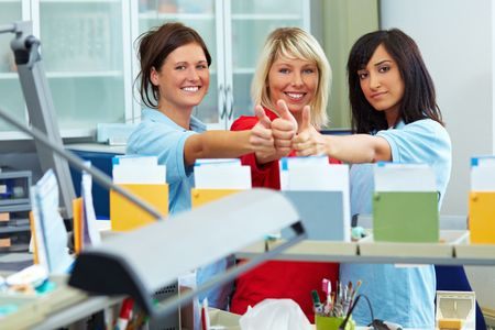 Three dental technicians showing her thumbs up photo