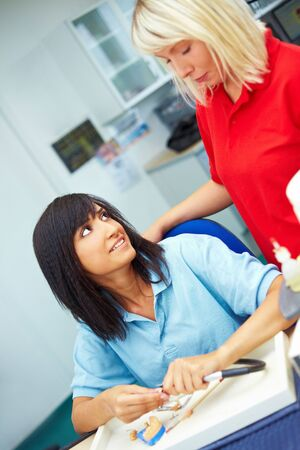 Two female dental technicians talking in laboratory photo