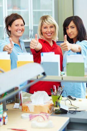 laboratorio dental: Tres t�cnicos de dental, mostrando sus pulgares
