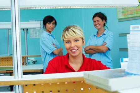 Three dental technicians in a dental laboratory photo